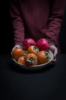 Herbstfrüchte und person, die plat hält