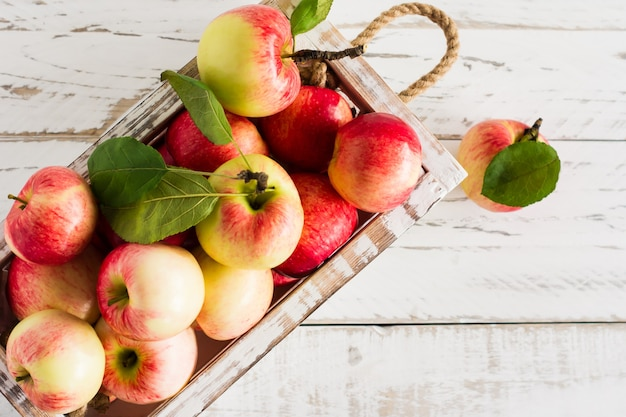 Herbstgartenäpfel in einer holzkiste auf einem weißen tisch. konzept von herbst und ernte.