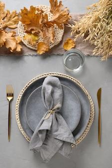 Herbstgedeck mit trockenen gelben eichenblättern, herbstdekoration und goldenem besteck auf grau.