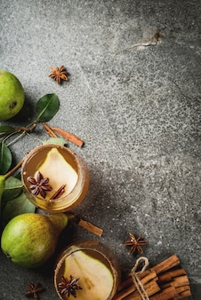 Herbstgetränke. glühwein. würziges cocktail des traditionellen herbstes mit birnen-, apfelwein- und schokoladensirup, mit zimt, anis, braunem zucker. auf schwarzem steintisch. ansicht von oben