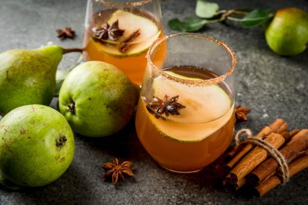 Herbstgetränke. glühwein. würziges cocktail des traditionellen herbstes mit birnen-, apfelwein- und schokoladensirup, mit zimt, anis, braunem zucker. auf schwarzem steintisch. copyspace