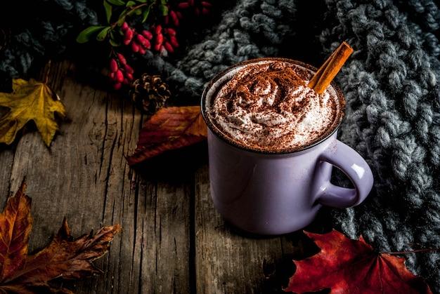 Herbstgetränke, heiße schokolade oder kakao mit schlagsahne und gewürzen (zimt, anis), auf dem alten rustikalen holztisch, mit einer warmen gemütlichen decke, einer heubeere und einem blattkopienraum