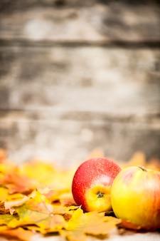 Herbstgrenze aus äpfeln und ahornblättern auf altem holzhintergrund