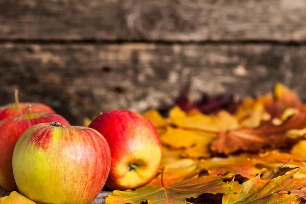 Herbstgrenze aus äpfeln und ahornblättern auf holzuntergrund
