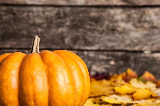 Herbstgrenze vom großen kürbis und von gelben blättern auf hölzernem hintergrund. geringe schärfentiefe