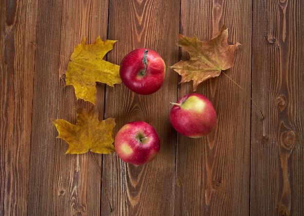 Herbstgrenze von äpfeln und gefallenen blättern auf altem holztisch.