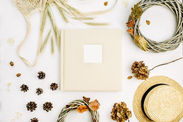 Herbstherbstkomposition mit hochzeits- oder familienfotoalbum, kranzrahmen, schnur schlecht, roggenohren, zapfen, trockene blätter auf weißer oberfläche