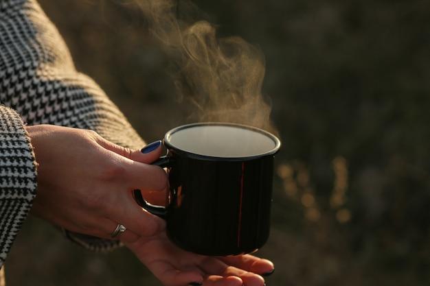 Herbstherbstkonzeptheißer kaffee in der handeine tasse heiße schokolade in den händen im herbstheißer kaffee