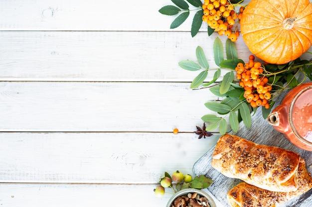 Herbsthintergrund. äpfel, kürbis, paradiesäpfel, eberesche auf weißem holz. draufsicht.