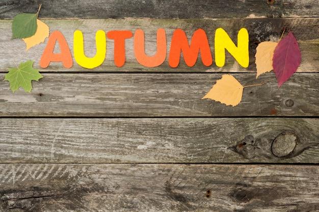 Herbsthintergrund auf altem hölzernem hintergrund, handgemachtes wort herbst aus filz, herbstlaub