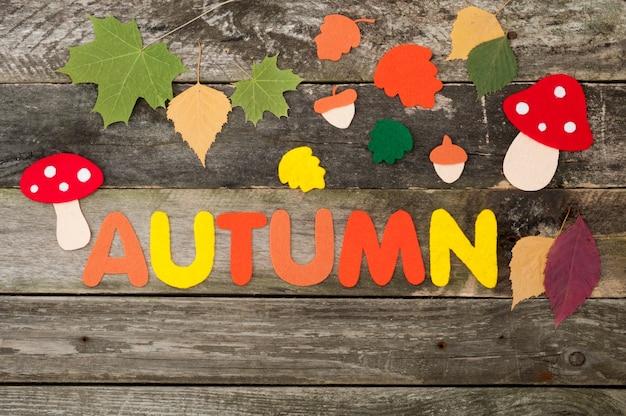 Herbsthintergrund auf altem hölzernen hintergrund, handgemachte blätter, pilze, eicheln und inschrift herbst aus filz
