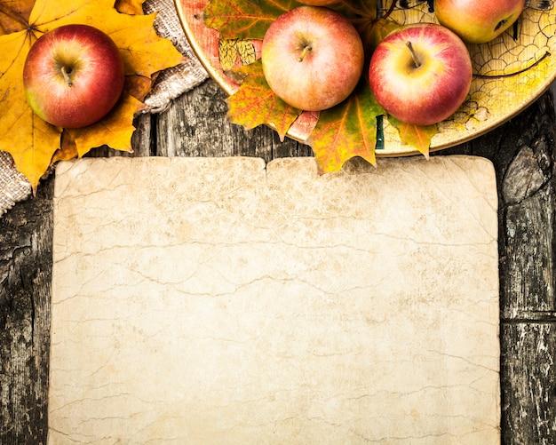 Herbsthintergrund aus äpfeln und ahornblättern auf holztisch. vintage-papier leer mit exemplar