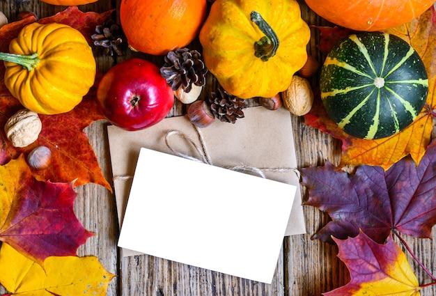 Herbsthintergrund im rahmen von geernteten kürbissen, äpfeln, nüssen und ahornblättern