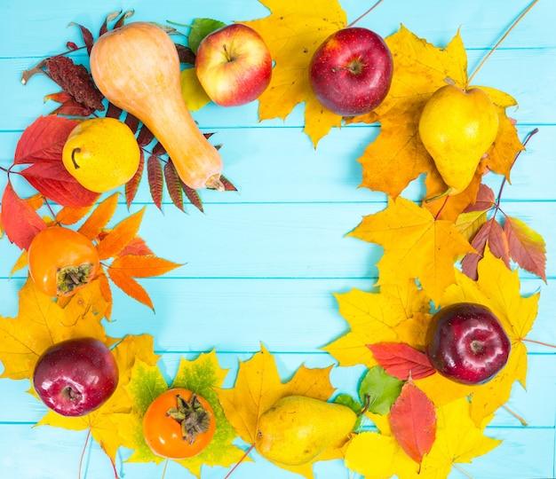 Herbsthintergrund mit blättern und ernte auf blauem hölzernem schreibtisch mit kopienraum.