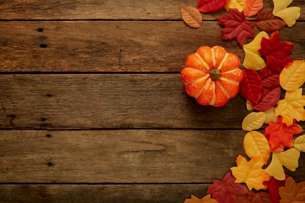 Herbsthintergrund mit blättern und kürbissen auf dunklem holz