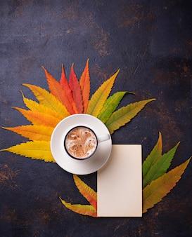 Herbsthintergrund mit blättern und tasse kaffee.