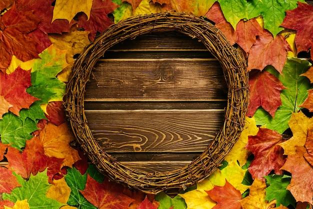 Herbsthintergrund mit farbigen blättern auf dunklem holzhintergrund mit platz für text