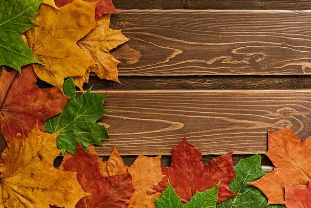 Herbsthintergrund mit farbigen blättern auf dunklem holzhintergrund