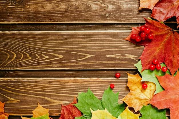 Herbsthintergrund mit farbigen blättern auf einem holzbrett. ein platz für ihren text. rahmenwinkel