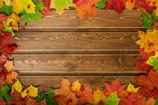 Herbsthintergrund mit farbigen blättern auf holzbrett