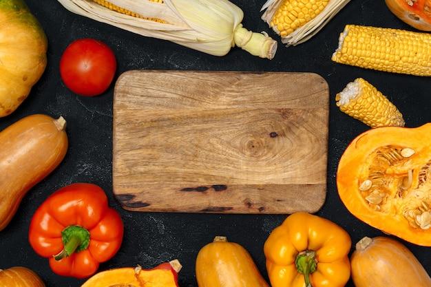 Herbsthintergrund mit frischem gemüse und hölzernem schneidebrett