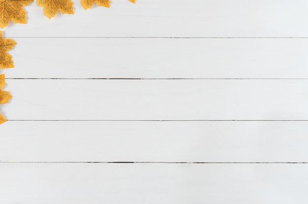Herbsthintergrund mit gelben ahornblättern auf weißem hölzernem hintergrund.