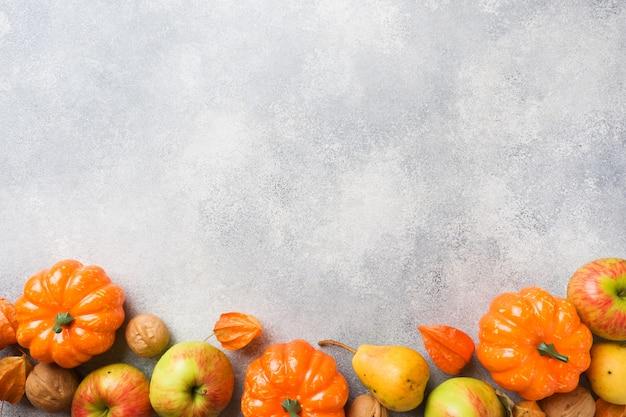 Herbsthintergrund mit gelben blättern, kürbisapfelbirnen und nüssen