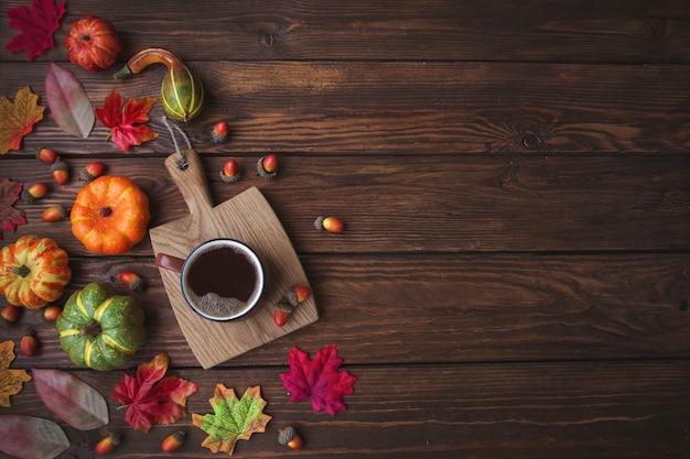 Herbsthintergrund mit kopienraum. tasse kaffee, kürbisse, blätter und eicheln auf einem holztisch.