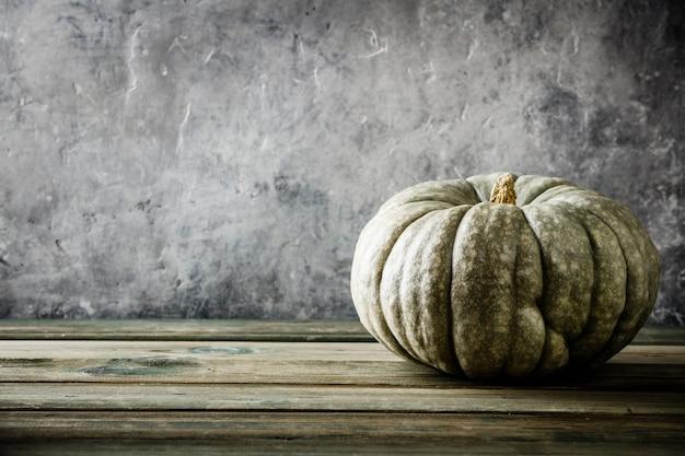 Herbsthintergrund mit kürbis auf hölzernem tabel gegen alte rostzustands-weinlesewand
