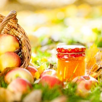 Herbsthintergrund mit marmelade im glas und roten saftigen äpfeln auf gelben blättern draußen