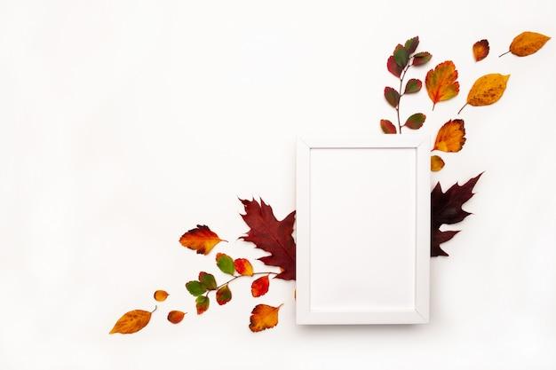 Herbsthintergrund mit natürlichem dekor. weißer fotorahmen, herbstgetrocknete blätter. flache lage, draufsicht. kopieren sie platz für saisonale aktionen und rabatte