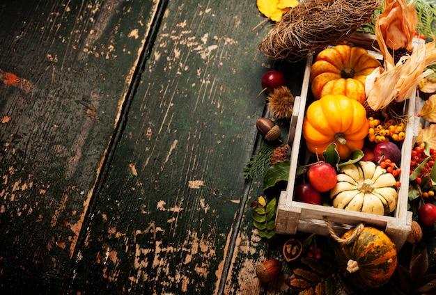 Herbsthintergrund mit saisonalen früchten, gemüse und blättern