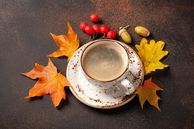 Herbsthintergrund mit tasse schwarzem kaffee
