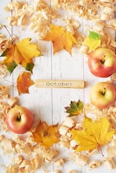 Herbsthintergrund von blättern, von äpfeln und von blumen.