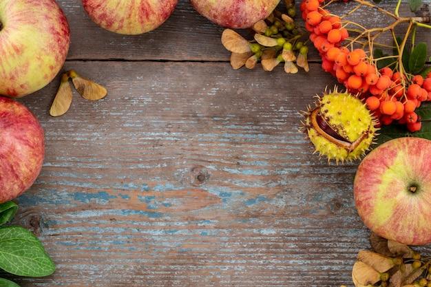 Herbsthintergrund von gefallenen blättern und früchten mit weinlese-gedeck auf altem holztisch. erntedankfest-konzept.