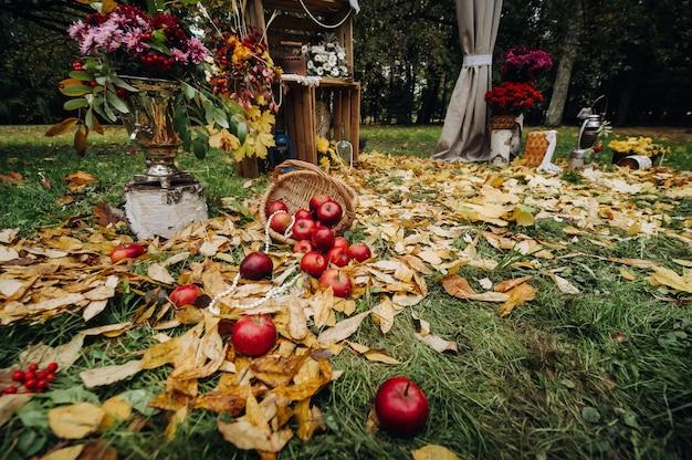 Herbsthochzeitszeremonie auf der straße auf dem grünen rasen. dekor mit bögen der frischen blumen für die zeremonie.