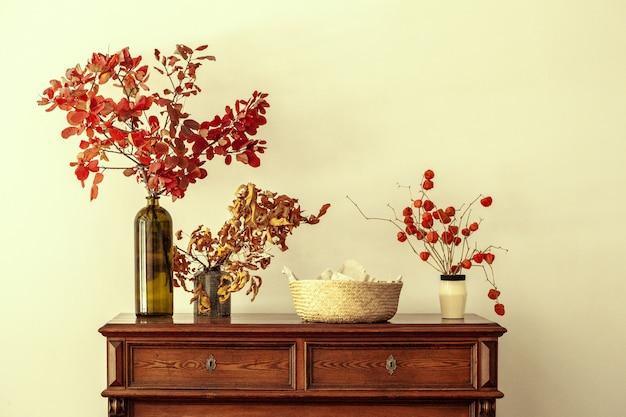 Herbstinnenausstattung mit trockenem blumenstrauß auf holzoberflächetabelle
