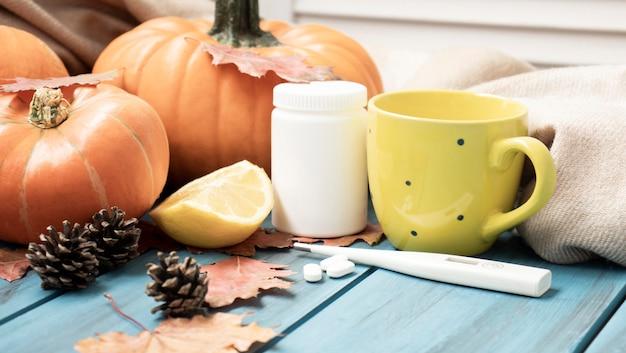 Herbstkälte, tee mit zitrone, thermometer, ingwer, kürbis, tabletten und trockenen blättern auf schwarzem grund. draufsicht, flach liegen