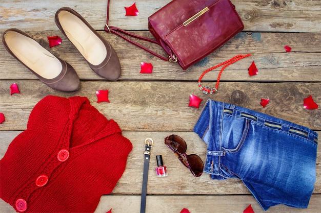 Herbstkleidung und -zubehör der frauen: rote strickjacke, jeans, handtasche, perlen, sonnenbrille, nagellack, schuhe, gürtel auf holz. ansicht von oben.