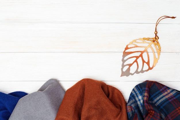Herbstkomfortkleidung für frauen, unterschiedlicher schal mit dekorativen blättern auf weißem holzhintergrund.