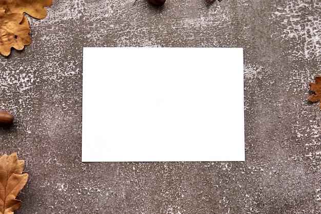 Herbstkomposition aus braunen getrockneten blättern und eicheln auf dunklem betonhintergrund. leeres papier des vorlagenmodells. herbst, halloween. flach legen, hintergrund kopieren.