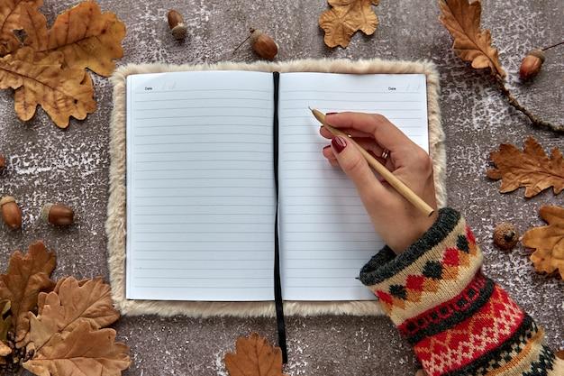Herbstkomposition aus braunen getrockneten blättern und eicheln auf dunklem betonhintergrund. vorlagenmodell leeres notizbuch und hand mit einem stift. herbst, halloween. flach legen, hintergrund kopieren.