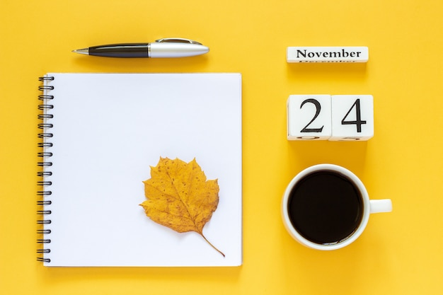 Herbstkomposition. holzkalender 24. november tasse kaffee, leerer offener notizblock