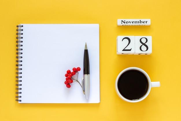 Herbstkomposition. holzkalender 28. november tasse kaffee, leerer offener notizblock mit stift und gelbem eichenblatt auf gelb