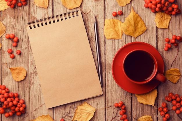 Herbstkomposition mit arbeitsbereich mit leerem bastelnotizbuch, bleistift, roter tasse kaffee und schönen roten ahornblättern. draufsicht, flache lage, vintage toning. herbst entspannungskonzept