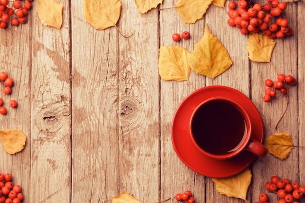 Herbstkomposition mit arbeitsbereich mit leerem notizbuch, bleistift, roter tasse kaffee und schönen roten ahornblättern. draufsicht, flache lage, vintage toning. herbst entspannungskonzept