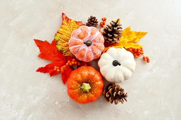 Herbstkomposition mit bunten blättern, tannenzapfen und kürbissen auf hellem hintergrund, kopierraum.