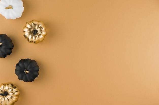Herbstkomposition mit dekorativen goldenen, weißen und schwarzen kürbissen