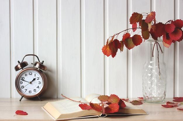 Herbstkomposition mit einem blumenstrauß in einer glasvase und einem offenen buch auf dem tisch september natürlichen hintergrund rustikales interieur mit wecker