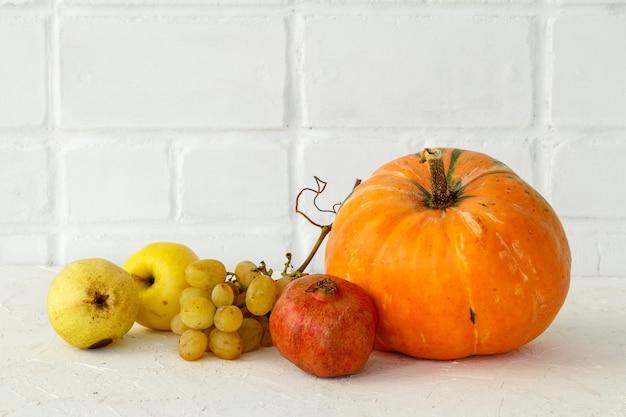 Herbstkomposition mit einem großen kürbis und früchten. kürbis und ein apfel, eine birne, ein granatapfel und eine traube auf weißem hintergrund. freier platz für text. herbst einkaufen. erntedankfest.